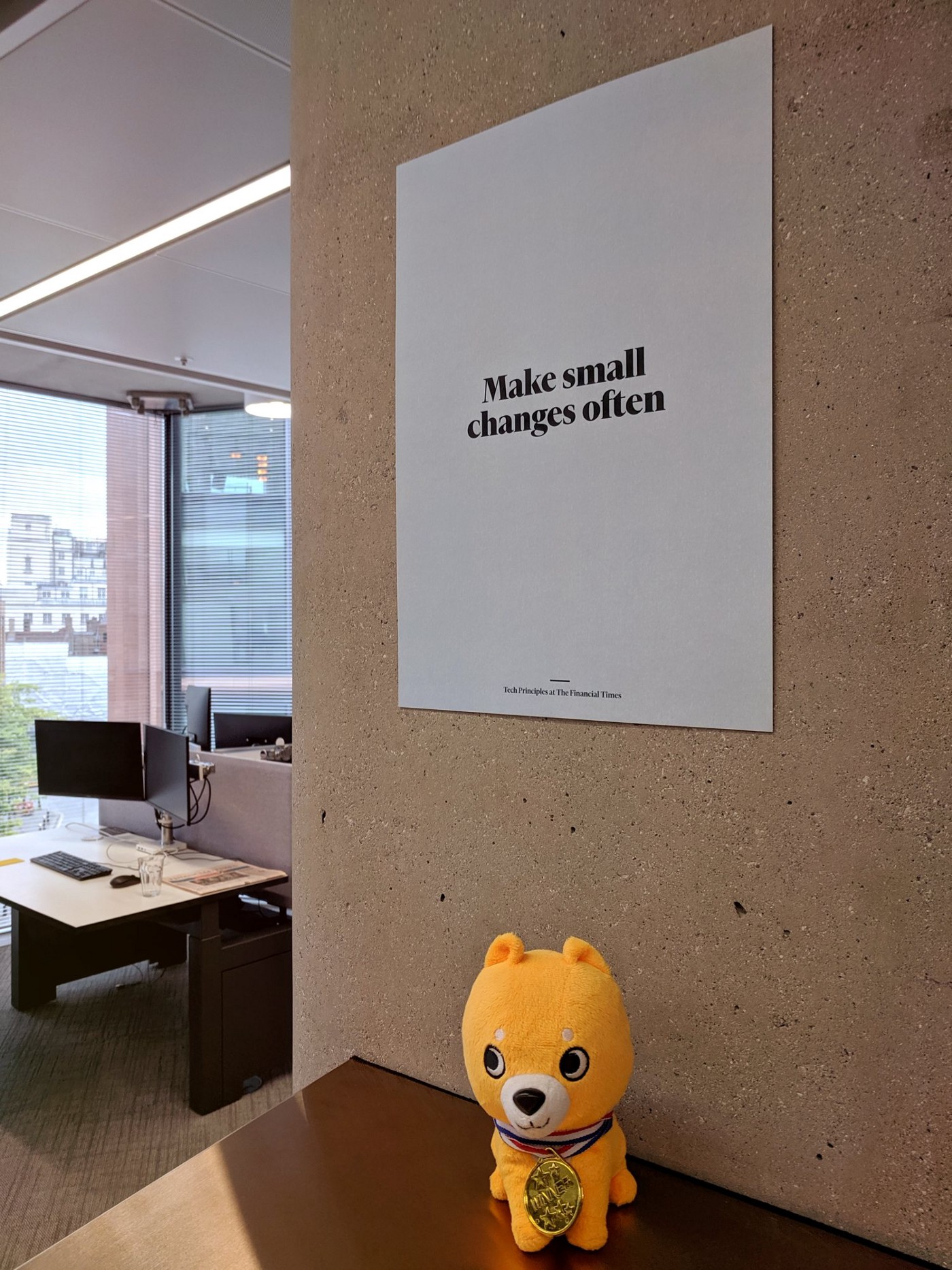 "A poster on the wall with the text ""Make small changes often"""